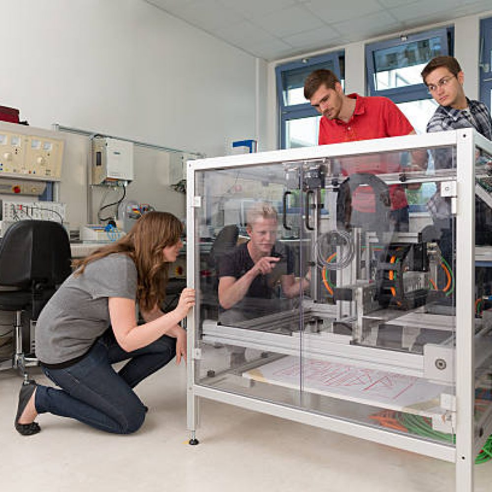 students working together in mechatronics laboratory of college