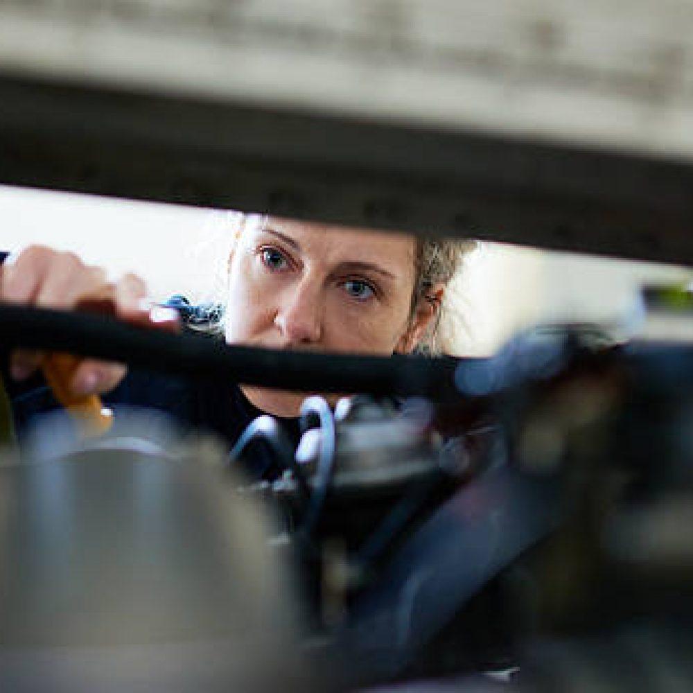 Female mechanic repairing engine of aircraft